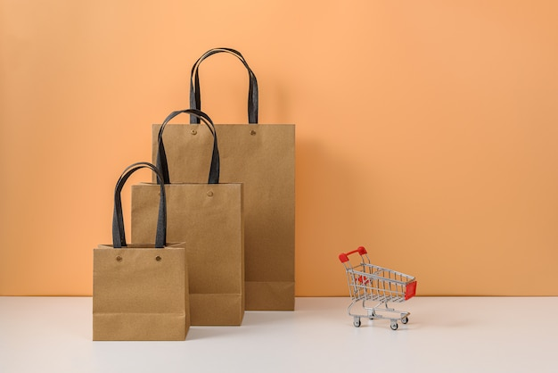 Sacolas de papel e carrinho de compras ou carrinho na mesa branca e parede laranja pastel