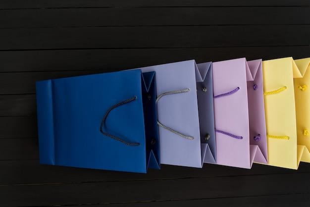 Sacolas de papel multicoloridas na superfície de madeira preta