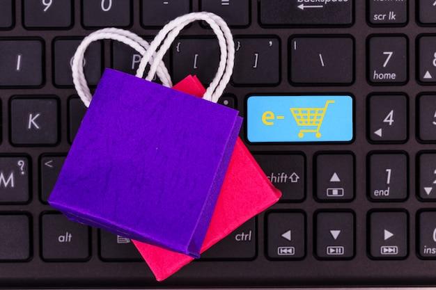 Sacolas de papel pequenas no teclado do laptop, botão esperando por compras on-line do cliente para confirmar e check-out. o conceito de pagamento em dinheiro digital on-line apenas busca e clica.