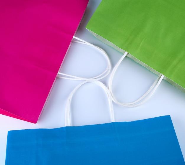 Sacolas de papel rosa, azul e verde com uma alça