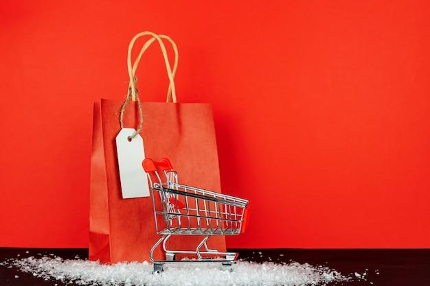Sacolas de papel vermelho e carrinho de compras de brinquedo pequeno na sala vermelha