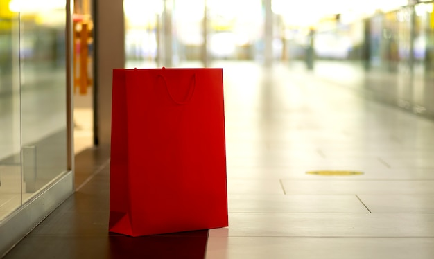 Sacolas de papel vermelho paradas no fundo do shopping