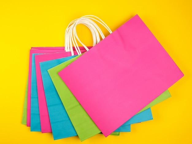 Sacolas retangulares de papel multicolorido com alças brancas