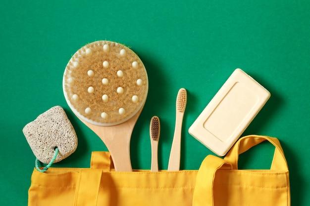 Sacos amigáveis de eco têxtil, sabão, escova de dentes de bambu, acessórios de sabão sobre um fundo verde. vista superior ou plana. conceito de zero desperdício e cuidado com o meio ambiente