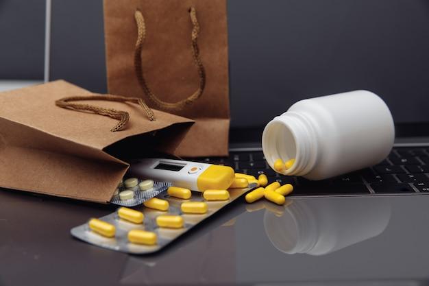 Sacos com comprimidos e drogas em um teclado de laptop. tema online de compra de medicamentos.