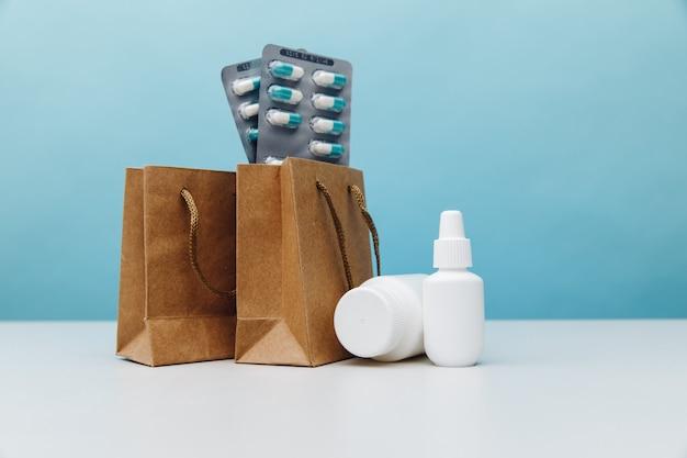 Sacos com recipientes brancos médicos e comprimidos sobre fundo azul, tema de compras online.