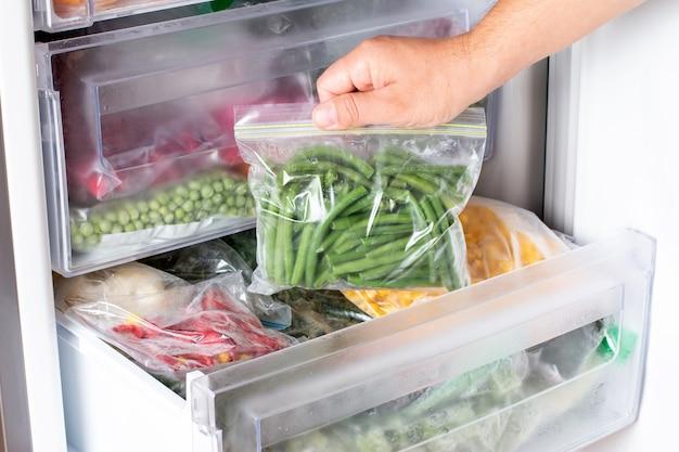 Sacos com vegetais congelados na geladeira. feijão verde congelado