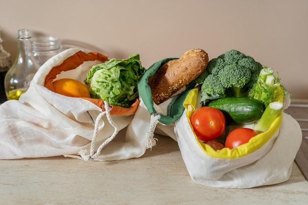 Sacos de algodão ecológicos com produtos alimentares na mesa. close up definir vela fundo de cor champanhe. comida orgânica local