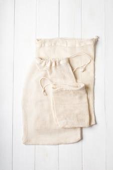 Sacos de algodão ecológicos na superfície branca