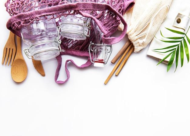 Sacos de algodão, saco de rede com potes de vidro reutilizáveis, bambu e talheres de madeira em fundo branco. conceito de desperdício zero. eco amigável. postura plana