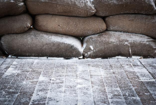 Sacos de areia marrons velhos no assoalho de madeira coberto de neve