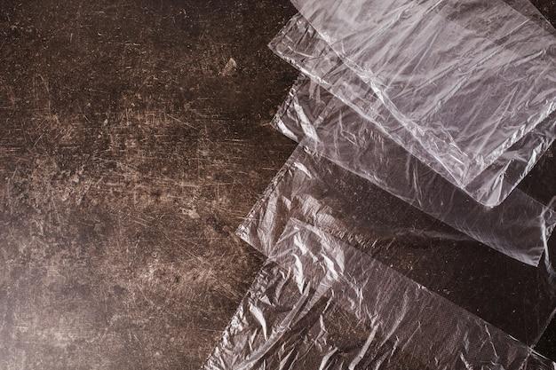 Sacos de celofane sobre um fundo escuro de mármore. polua a natureza. conceito eco