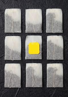 Sacos de chá de chá preto com etiqueta amarela em fundo preto. vista do topo