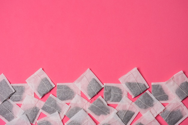 Sacos de chá de ervas branco em fundo rosa