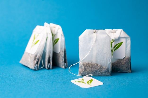 Sacos de chá de ervas verdes sobre um fundo azul.
