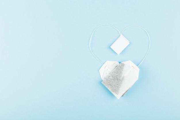 Sacos de chá em forma de coração sobre fundo azul.