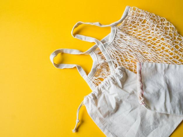 Sacos de compras bege eco-amigáveis, saco de corda no fundo amarelo.