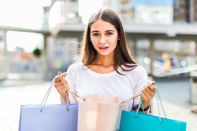 Sacos de compras coloridos da mulher feliz comprador e apontando-lhe na rua