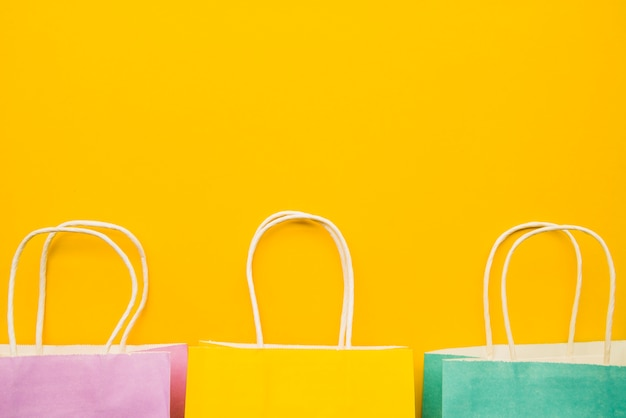Sacos de compras coloridos na mesa amarela