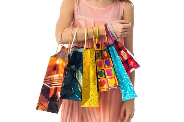 Sacos de compras coloridos pendurados na mão de uma garota.