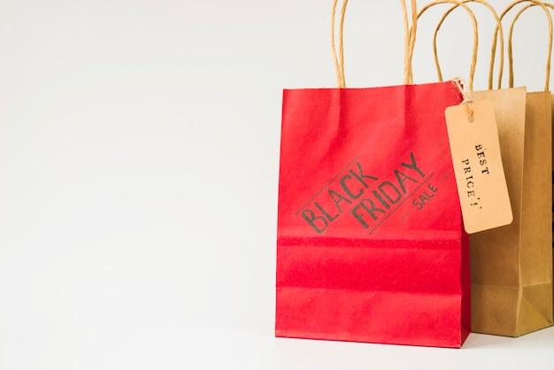 Sacos de compras de papel vermelho e marrom com etiqueta de venda