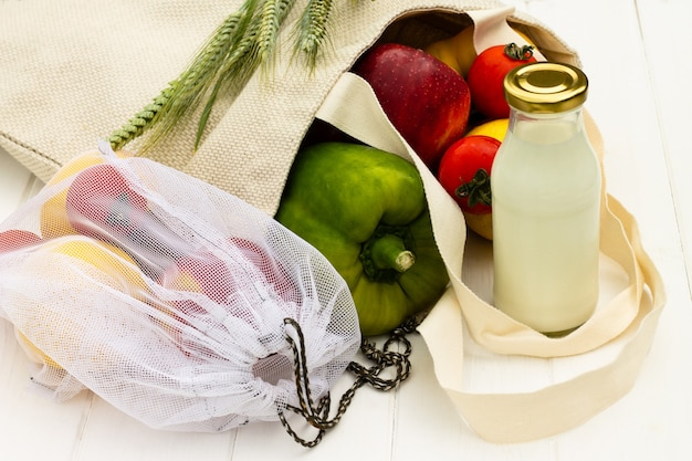 Sacos de compras de tecido de algodão com legumes e frutas e uma garrafa de vidro de leite em um fundo branco de madeira. resíduos zero e conceito ecológico.