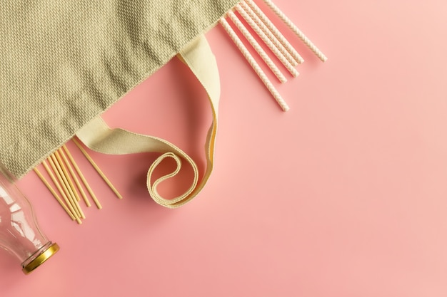 Sacos de compras de tecido de algodão, garrafas de vidro, canudos de papel e palitos de madeira em um fundo rosa. vista do topo. copie o espaço.