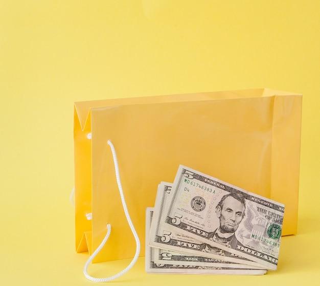 Sacos de compras e dólares em um fundo amarelo.