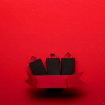 Sacos de compras e fita vermelha conceito preto sexta-feira