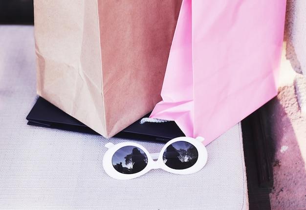 Sacos de compras e óculos de sol brancos. estilo de vida de mulheres jovens.