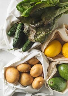 Sacos de compras ecológicos têxteis com frutas e legumes em fundo branco