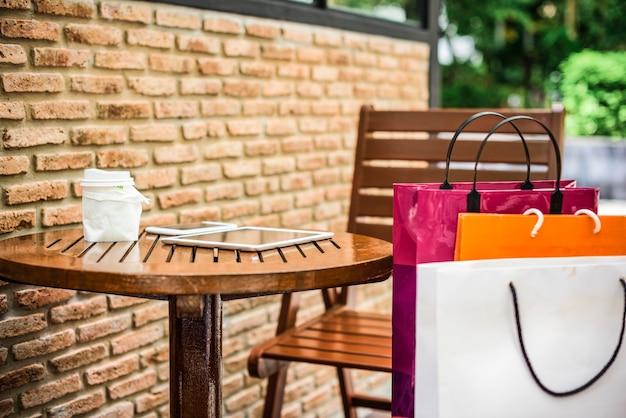Sacos de compras em um café ao ar livre
