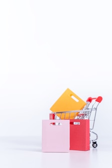 Sacos de compras em um carrinho de compras vermelho prata isolado no fundo da mesa branca, conceito de ficar em casa, close-up, copie o projeto do espaço.
