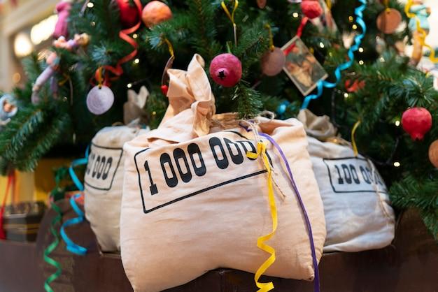 Sacos de dinheiro sob a árvore de natal.