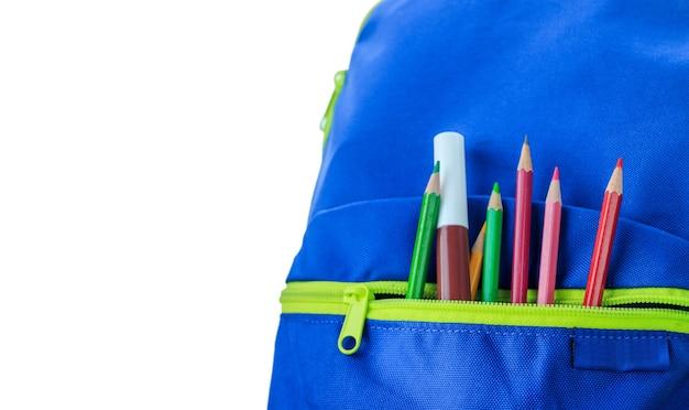 Sacos de escola, livros, lápis, pastéis, isolados no fundo branco.