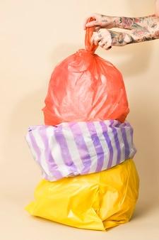 Sacos de lixo coloridos em fundo amarelo
