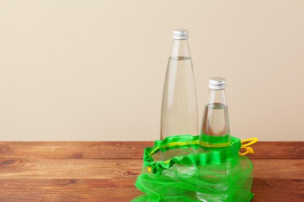 Sacos de malha com garrafa de água de vidro reutilizável. estilo de vida sustentável. zero conceito de desperdício. sem plástico.