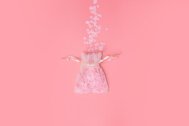 Sacos de organza na textura de fundo rosa com lindas flores saindo, margaridas brancas, primavera, dia das mães, amor, conceito mínimo de férias.