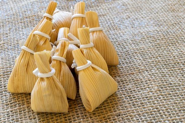 Sacos de palha de milho com doce de leite em toalha de mesa de juta