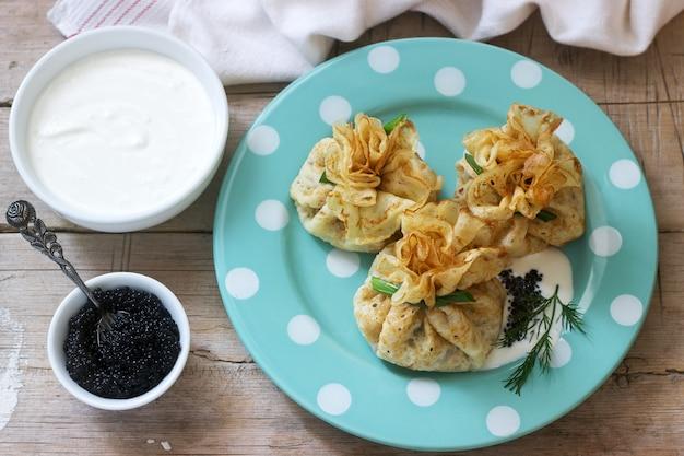 Sacos de panquecas recheadas com arenque, servido com caviar, creme de leite e endro em um fundo de madeira. estilo rústico.