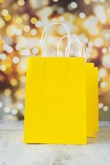 Sacos de papel amarelo com efeito bokeh