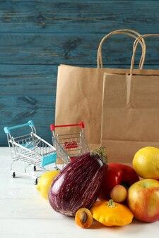 Sacos de papel, carrinhos de compras, vegetais e frutas na mesa de madeira