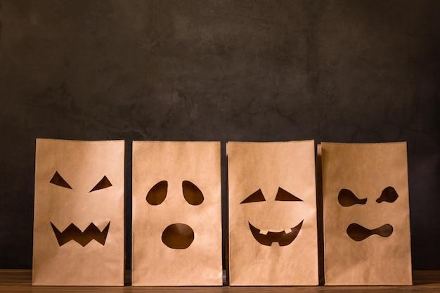 Sacos de papel com cara assustadora na mesa de madeira