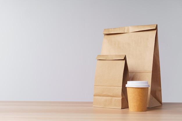 Sacos de papel com recipientes para levar comida e copos de café