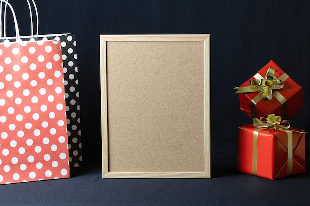 Sacos de papel de bolinhas, quadro de cortiça e caixas de presente de natal com espaço de cópia