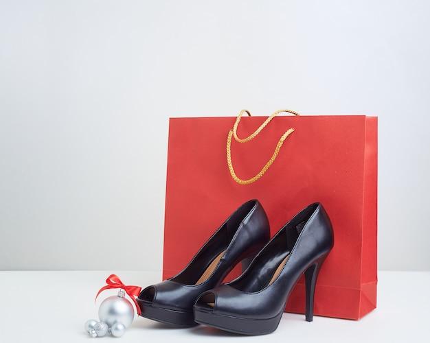 Sacos de papel de compras de natal com sapatos de salto altos