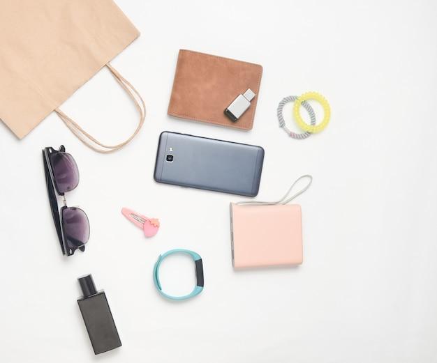 Sacos de papel e muitas compras de gadgets e acessórios em um fundo branco: óculos de sol, smartphone, pulseira inteligente, banco de powel, unidade flash usb, carteira. conceito de consumidor. vista do topo.