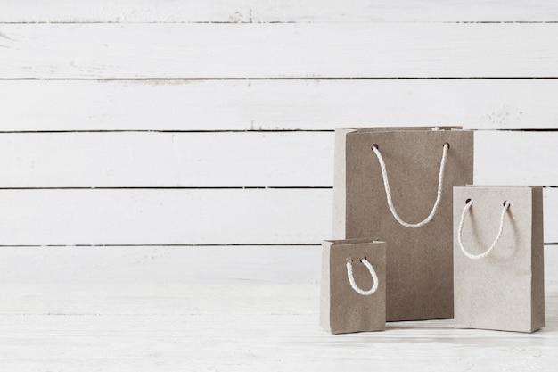Sacos de papel em fundo branco de madeira
