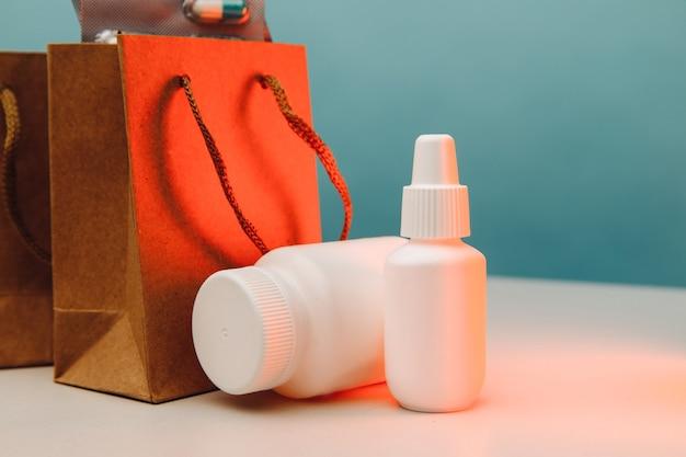 Sacos de papel temáticos de compras on-line com recipientes brancos médicos e closeup de pílulas