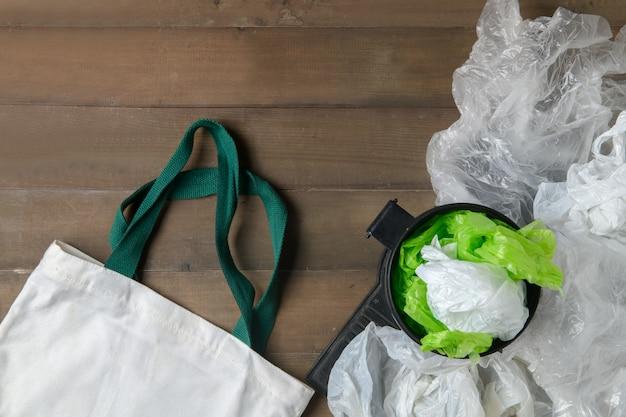 Sacos de plástico em caixa e sacola de lona em madeira